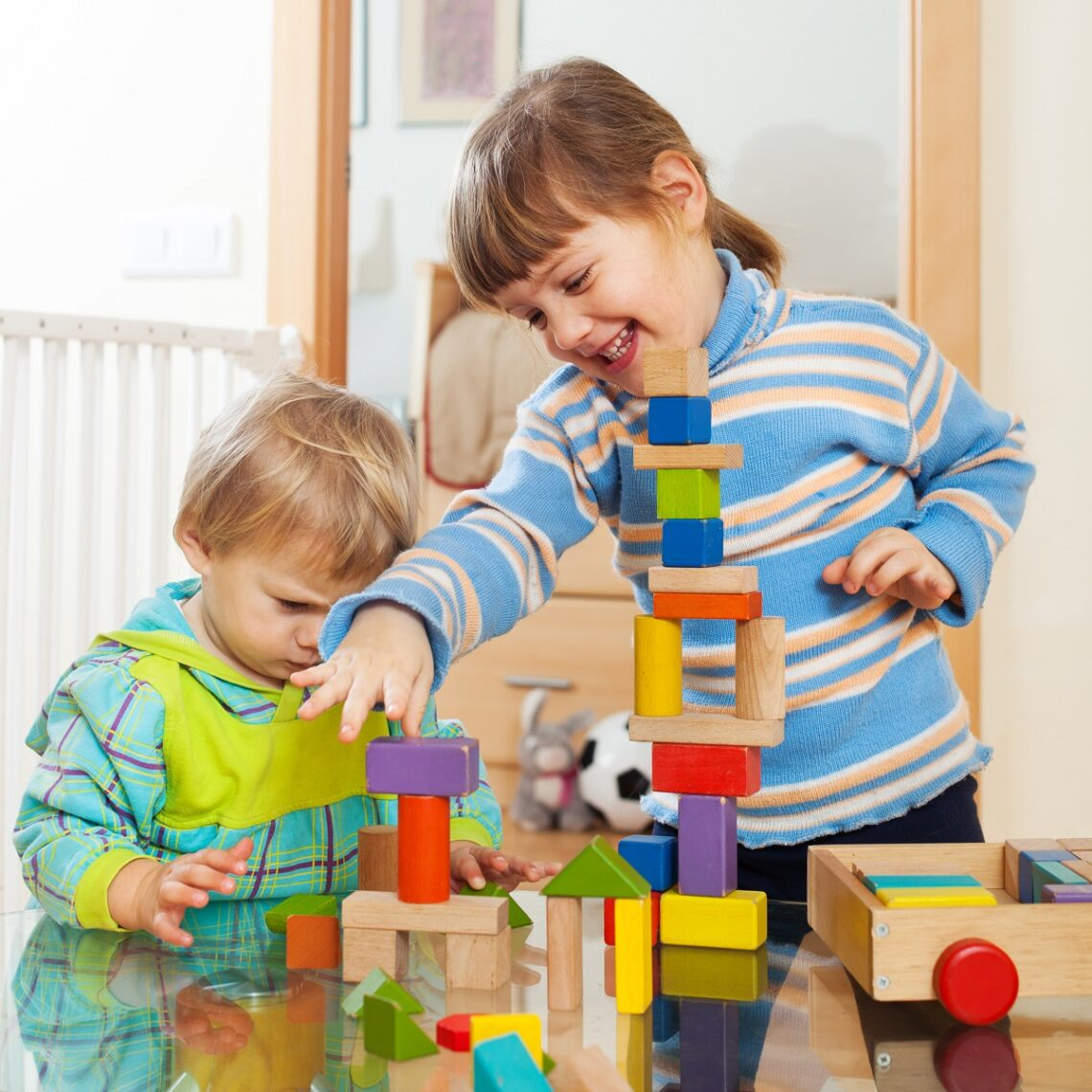 siblings together playing with  toys in home