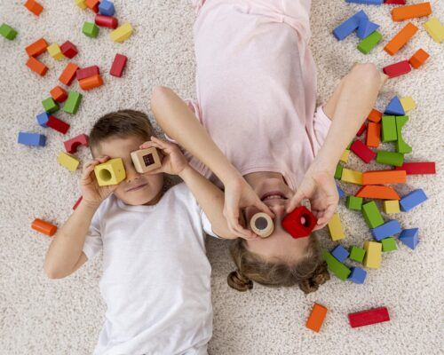 top-view-non-binary-kids-playing-with-colorful-game